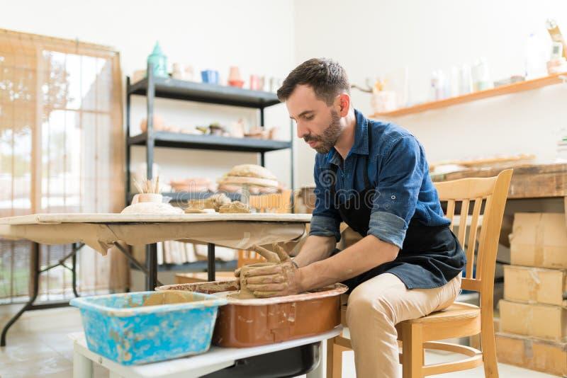 Αγγειοπλάστης που δημιουργεί τη δημιουργική αγγειοπλαστική καθμένος στο εργαστήριο στοκ φωτογραφίες με δικαίωμα ελεύθερης χρήσης