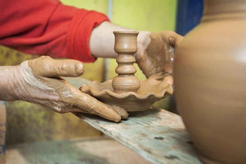 Αγγειοπλάστης με την τοποθέτηση σε έναν πίνακα του ξύλινου κατόχου κεριών του freshl στοκ φωτογραφίες