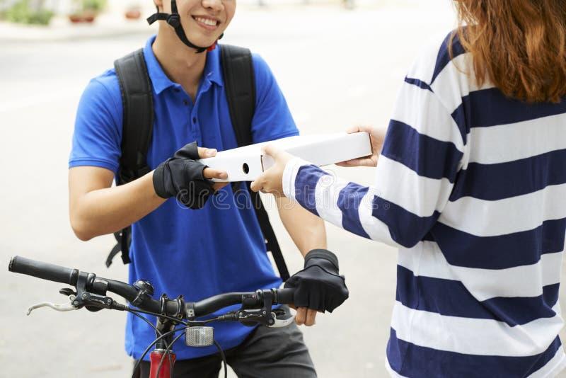 Αγγελιαφόρος που δίνει το κιβώτιο πιτσών στον πελάτη στοκ εικόνες