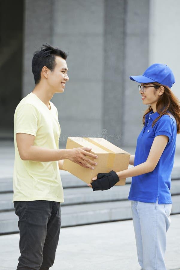 Αγγελιαφόρος που δίνει το κουτί από χαρτόνι στοκ φωτογραφία