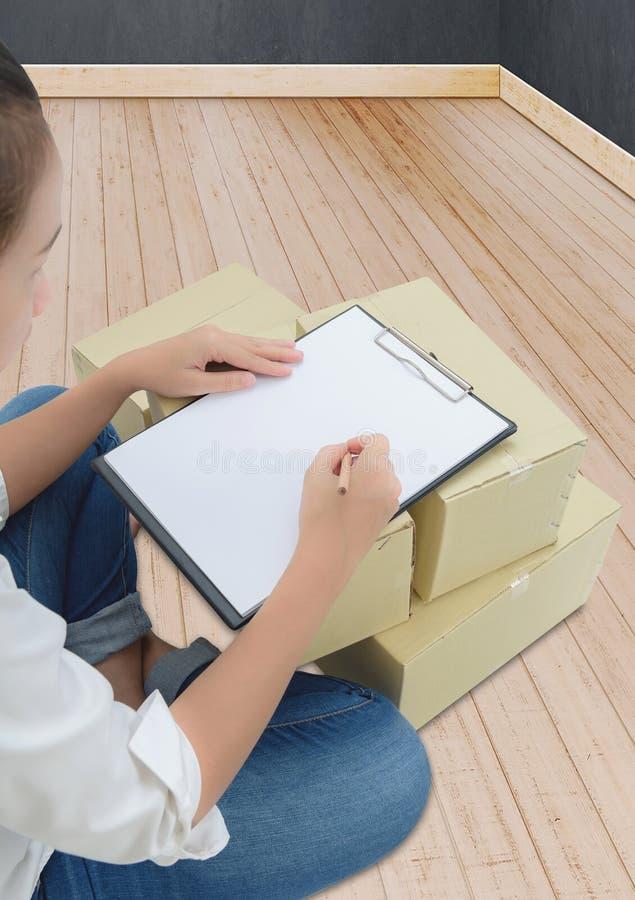 Αγγελιαφόρος που κάνει τις σημειώσεις στην παραλαβή παράδοσης μεταξύ των δεμάτων στα κιβώτια στοκ φωτογραφία
