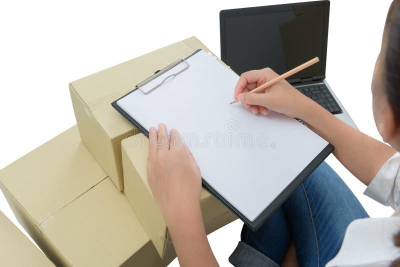 Αγγελιαφόρος που κάνει τις σημειώσεις στην παραλαβή παράδοσης μεταξύ των δεμάτων στα κιβώτια στοκ εικόνες με δικαίωμα ελεύθερης χρήσης