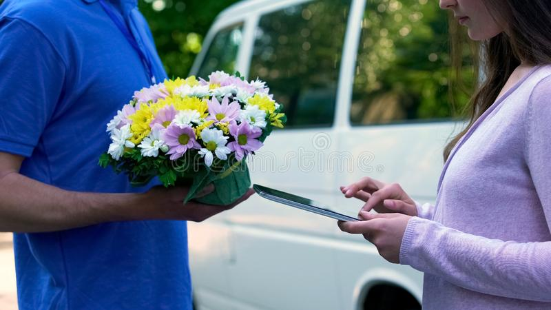 Αγγελιαφόρος που παραδίδει τη γυναίκα λουλουδιών, υπογραφή ταμπλετών, υπηρεσία παρόντος γενεθλίων στοκ φωτογραφίες με δικαίωμα ελεύθερης χρήσης