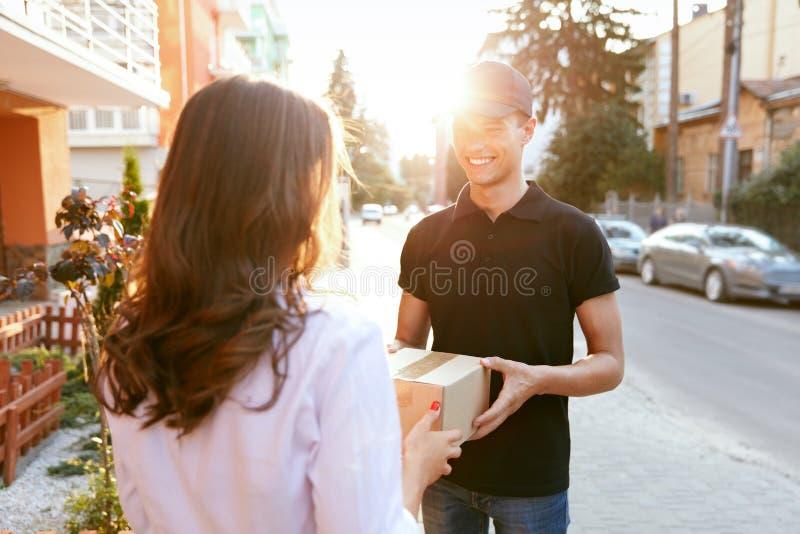 Αγγελιαφόρος που παραδίδει τη συσκευασία στη γυναίκα Πελάτης που λαμβάνει το κιβώτιο στοκ εικόνες με δικαίωμα ελεύθερης χρήσης
