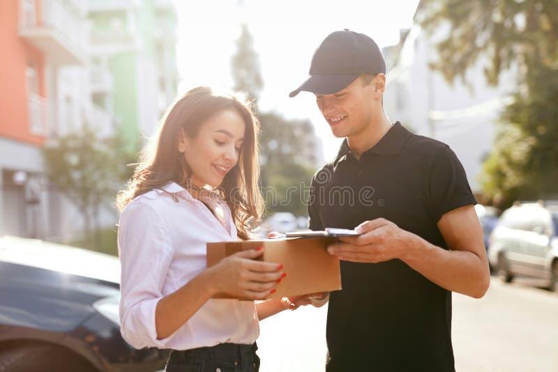 Αγγελιαφόρος που παραδίδει τη συσκευασία στη γυναίκα, πελάτης που υπογράφει το έγγραφο στοκ εικόνα με δικαίωμα ελεύθερης χρήσης