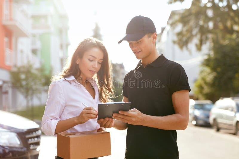 Αγγελιαφόρος που παραδίδει τη συσκευασία στη γυναίκα, πελάτης που υπογράφει το έγγραφο στοκ εικόνες με δικαίωμα ελεύθερης χρήσης