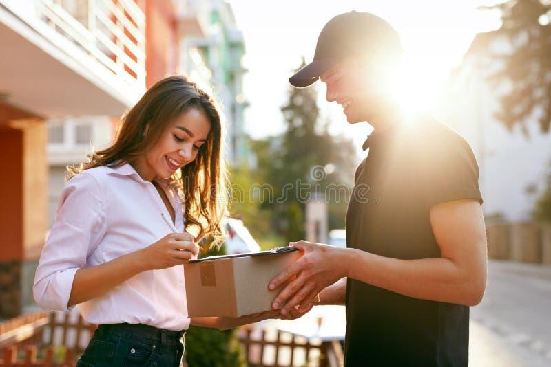 Αγγελιαφόρος που παραδίδει τη συσκευασία στη γυναίκα, πελάτης που υπογράφει το έγγραφο στοκ φωτογραφία με δικαίωμα ελεύθερης χρήσης