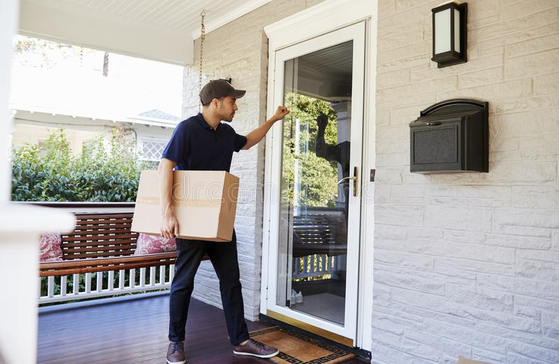 Αγγελιαφόρος που χτυπά στην πόρτα του σπιτιού για να παραδώσει τη συσκευασία στοκ εικόνες