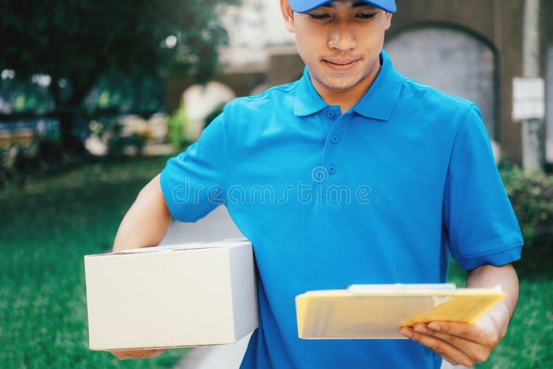 Αγγελιαφόρος υπηρεσιών παράδοσης που στέκεται μπροστά από το σπίτι με τα κιβώτια στοκ φωτογραφίες