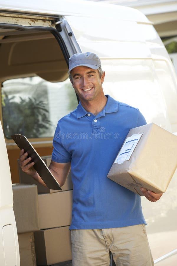 Αγγελιαφόρος που παραδίδει τη συσκευασία με το φορτηγό στοκ εικόνες