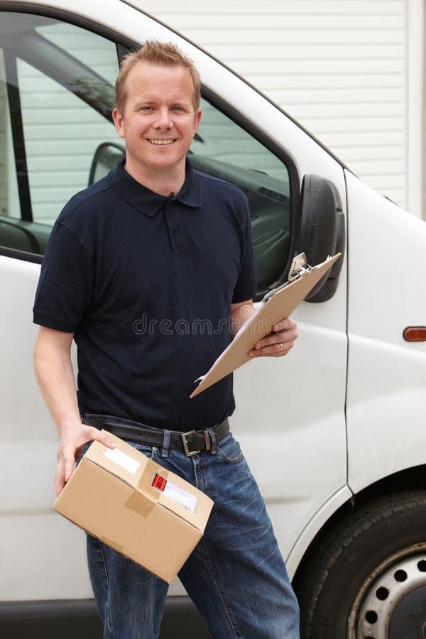 Αγγελιαφόρος που παραδίδει τη συσκευασία που στέκεται δίπλα στο φορτηγό στοκ εικόνες
