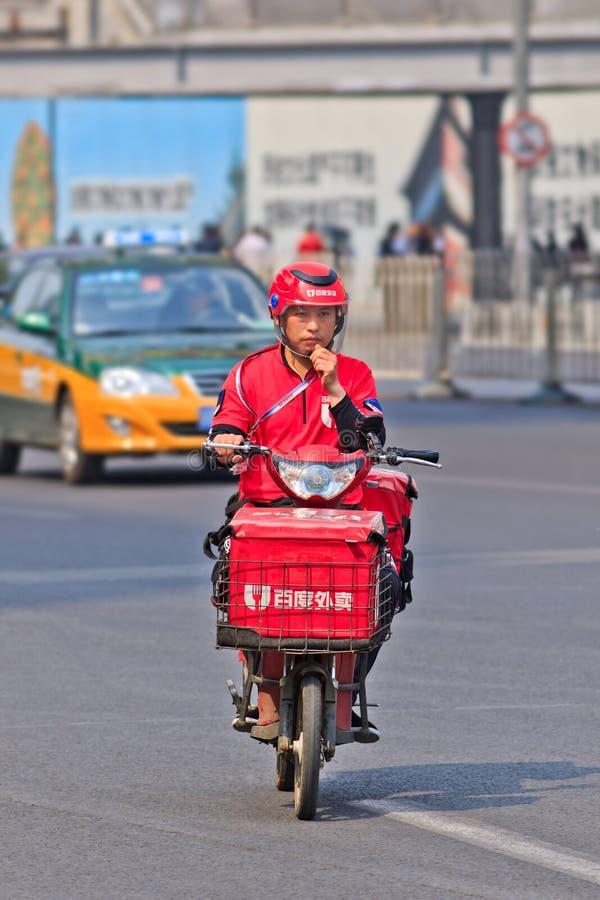 Αγγελιαφόρος τροφίμων ε-ποδηλάτων στο δρόμο, Πεκίνο, Κίνα στοκ εικόνες