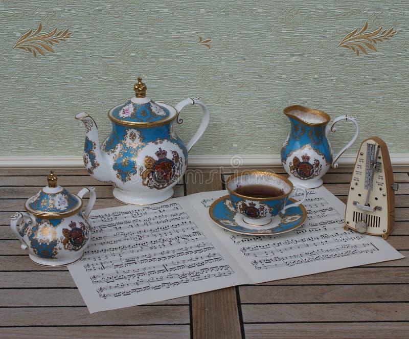 Αγγλική φλυτζάνα τσαγιού με το πιατάκι, teapot, το κύπελλο ζάχαρης και την κανάτα και το μετρονόμο κρέμας για τη μουσική σε ένα φ στοκ εικόνες