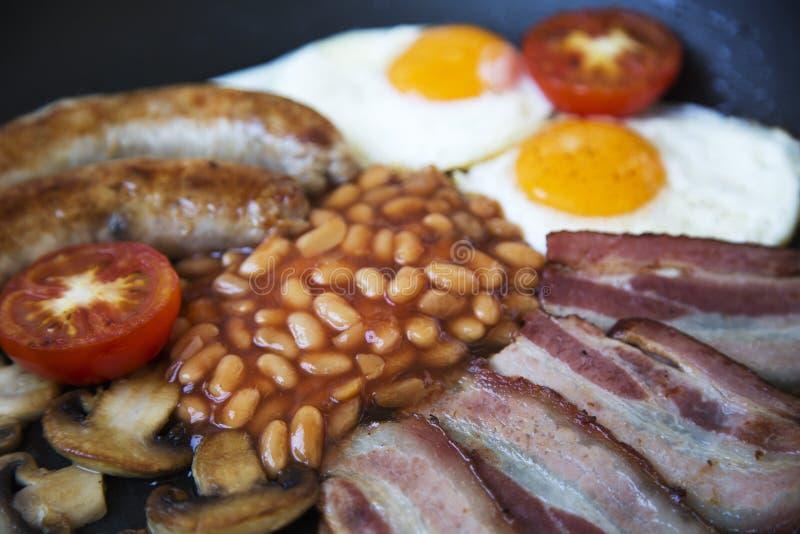 Αγγλικό πρόγευμα Ull σε ένα τηγανίζοντας τηγάνι με τα τηγανισμένες αυγά, το μπέϊκον, τα λουκάνικα, τα φασόλια και τις φρυγανιές στοκ εικόνα
