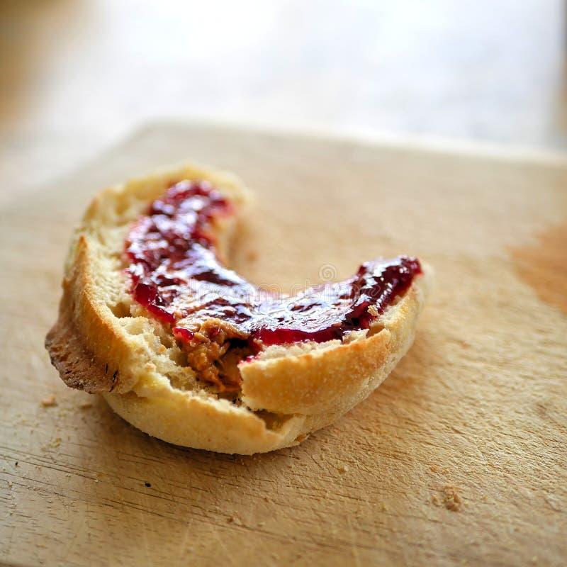 Αγγλικό muffin για το πρόγευμα, με τη γλυκιά κόκκινη μαρμελάδα ή τη ζελατίνα που διαδίδεται στην κορυφή, που κάθεται στον ξύλινο  στοκ φωτογραφία με δικαίωμα ελεύθερης χρήσης