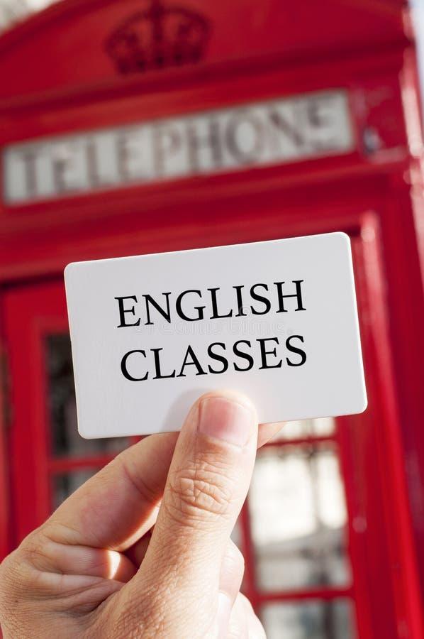 Αγγλικές κατηγορίες κειμένων σε μια πινακίδα και έναν κόκκινο τηλεφωνικό θάλαμο στοκ εικόνες με δικαίωμα ελεύθερης χρήσης