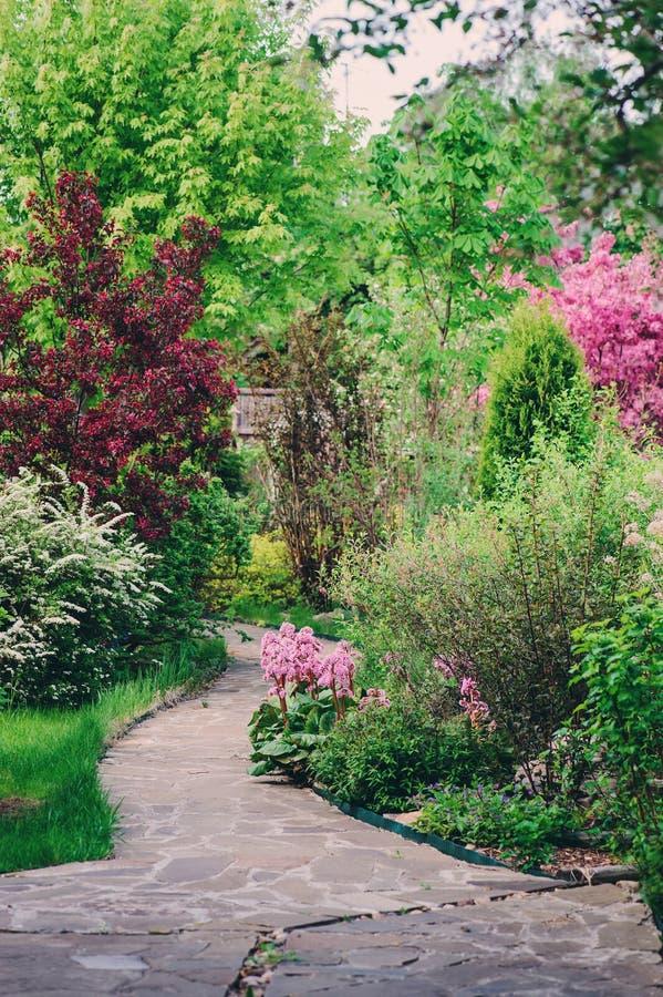Αγγλικός κήπος την άνοιξη Όμορφη άποψη με τα ανθίζοντας δέντρα και τους θάμνους στοκ φωτογραφία