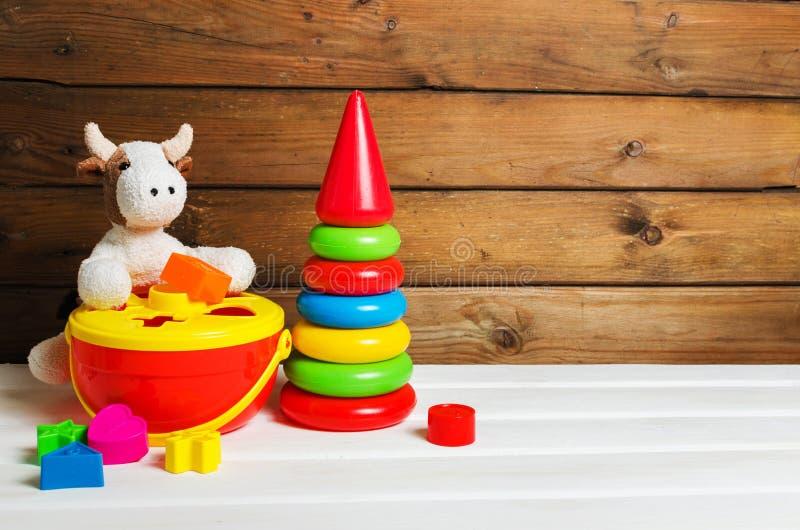 Αγελάδα βελούδου και πλαστικό παιχνίδι συσσώρευσης στο άσπρο ξύλινο υπόβαθρο ζωηρόχρωμη πυραμίδα Ζωηρόχρωμος διαλογέας στοκ φωτογραφία με δικαίωμα ελεύθερης χρήσης