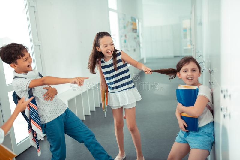 Αγενή βίαια παιδιά σχετικά με την τρίχα του κοριτσιού φοβερίζοντας την στοκ εικόνες