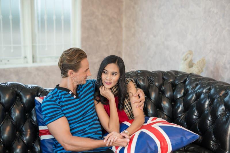 Αγκάλιασμα δύο νέο εραστών, που κάθεται στον καναπέ στοκ φωτογραφία με δικαίωμα ελεύθερης χρήσης