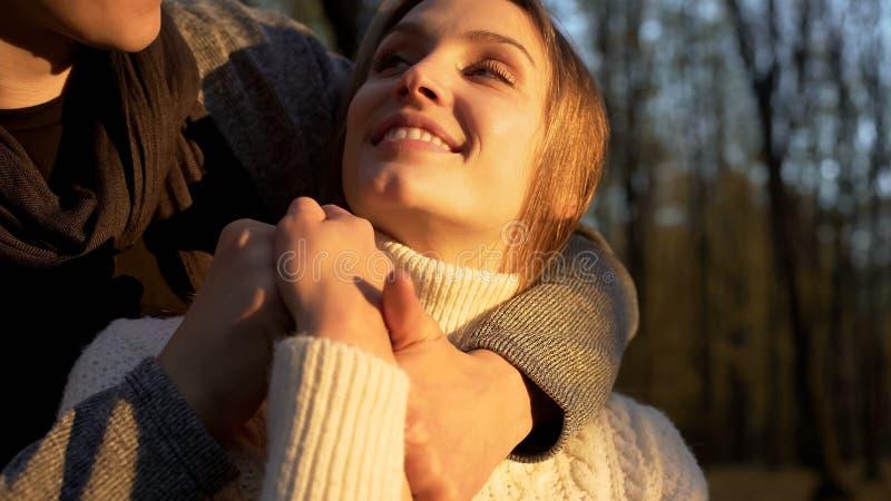 Αγκάλιασμα ζευγών σπουδαστών, που χρονολογεί μετά από τις κατηγορίες στο πανεπιστημιακό πάρκο, ημερομηνία φθινοπώρου στοκ φωτογραφίες