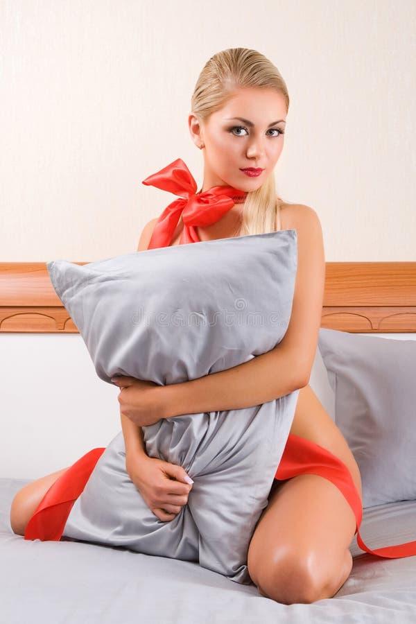 αγκάλιασμα των νεολαιών γυναικών μαξιλαριών στοκ εικόνες