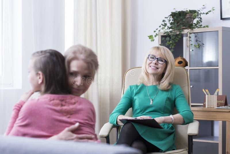 Αγκαλιάζοντας κατά τη διάρκεια της οικογένειας τη σύνοδο παροχής συμβουλών στοκ εικόνες