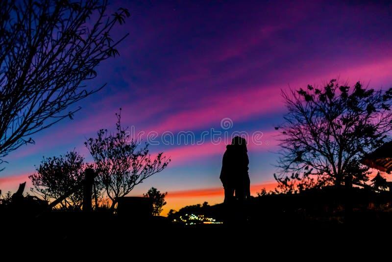 Αγκαλιά ανδρών και γυναικών ζεύγους σκιαγραφιών με ευτυχώς μεταξύ του όμορφου ουρανού ηλιοβασιλέματος στη φύση στοκ φωτογραφία