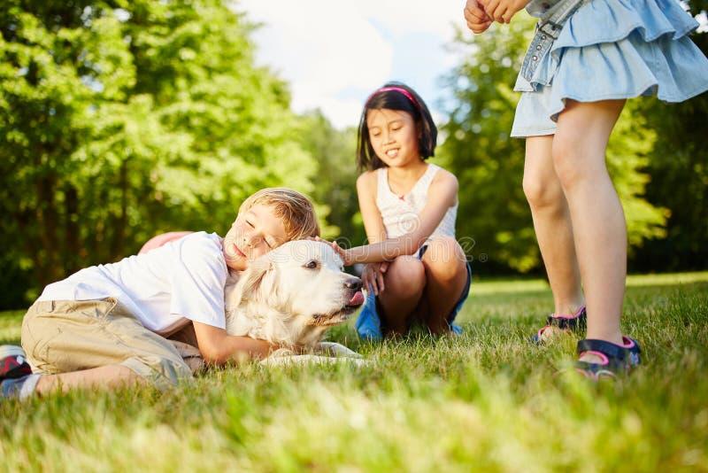Αγκαλιές αγοριών με χρυσό Retriever στοκ εικόνες με δικαίωμα ελεύθερης χρήσης