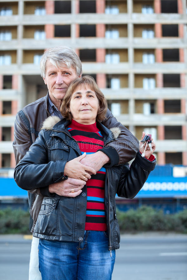 Αγκαλιάζοντας το αγαπώντας ανώτερο ζεύγος με το κλειδί σπιτιών υπό εξέταση στοκ εικόνες