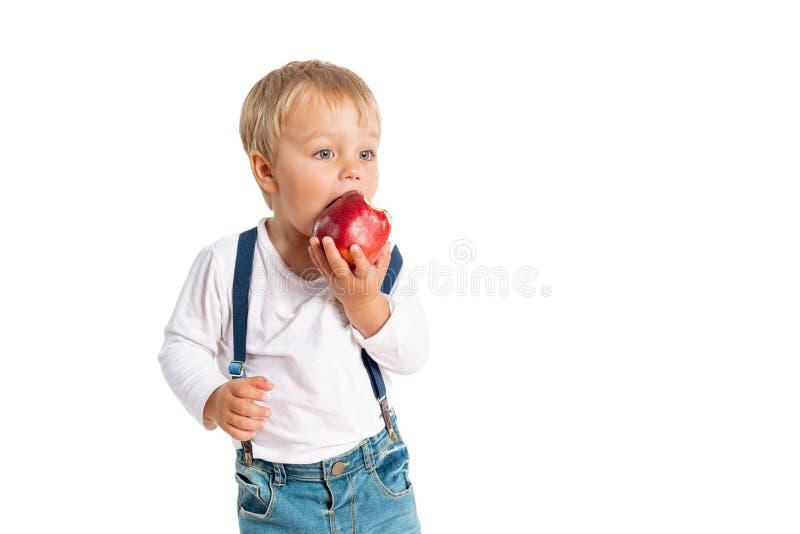Αγοράκι που τρώει το μήλο και που χαμογελά στο στούντιο που απομονώνεται στο άσπρο υπόβαθρο στοκ φωτογραφία