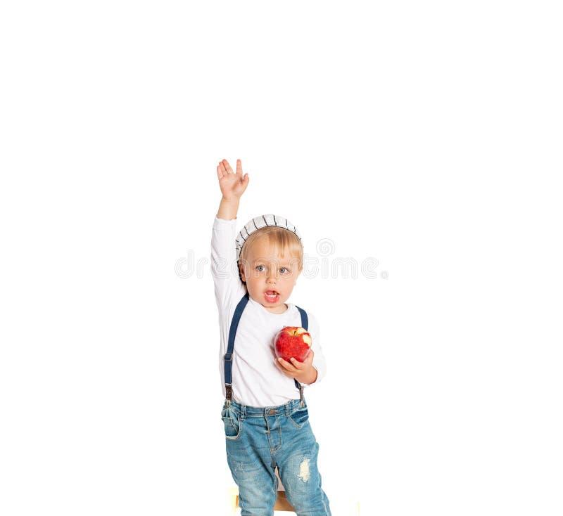 Αγοράκι που τρώει το μήλο και που χαμογελά στο στούντιο που απομονώνεται στο άσπρο υπόβαθρο στοκ φωτογραφίες