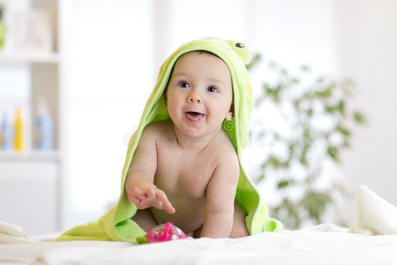 Αγοράκι που φορά την πάνα και την πράσινη πετσέτα στην άσπρη ηλιόλουστη κρεβατοκάμαρα στοκ εικόνα με δικαίωμα ελεύθερης χρήσης