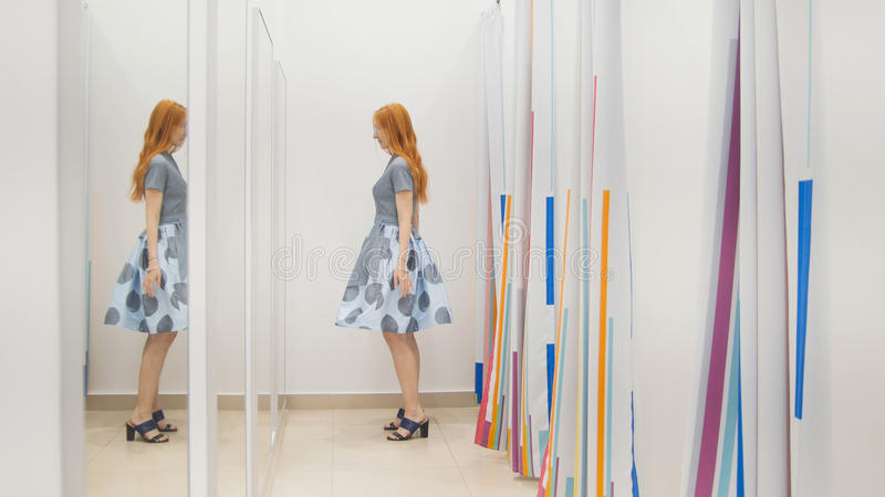Αγορές για τη γυναίκα Ένα κορίτσι που προσπαθεί σε ένα φόρεμα μπροστά από έναν καθρέφτη στοκ φωτογραφία με δικαίωμα ελεύθερης χρήσης