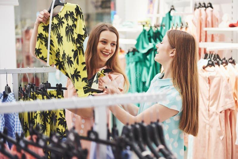 Αγορές με το bestie Οπισθοσκόπος δύο όμορφων γυναικών με τις αγορές τοποθετεί την εξέταση τη κάμερα με το χαμόγελο σε σάκκο περπα στοκ εικόνες