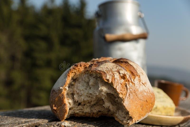 Αγροτικά καρδάρι ψωμιού και γάλακτος σε έναν ξύλινο πίνακα στοκ εικόνες με δικαίωμα ελεύθερης χρήσης
