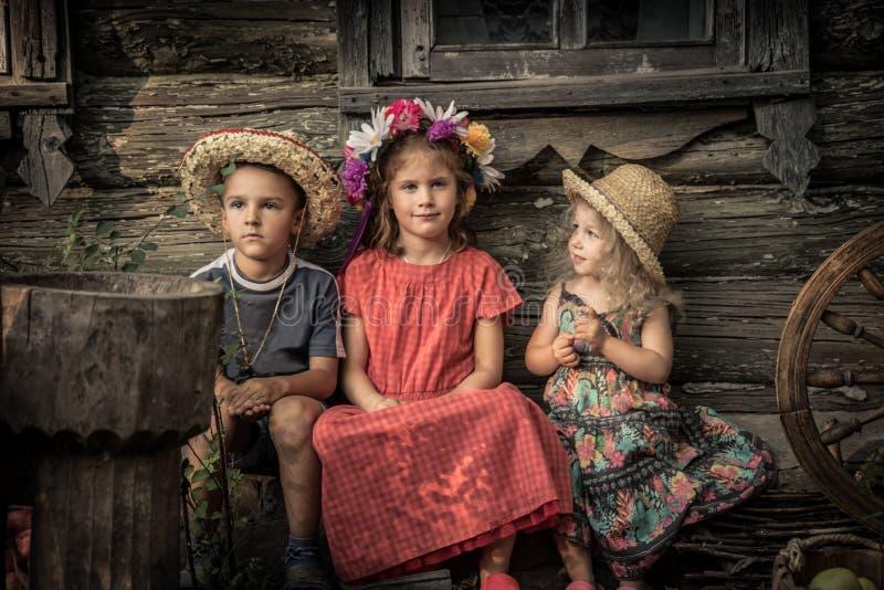 Αγροτικά παιδιά τρόπου ζωής επαρχίας που κάθονται μαζί το παλαιό σπίτι επαρχίας που συμβολίζει τη φιλία παιδιών και το ευτυχές ξέ στοκ φωτογραφία