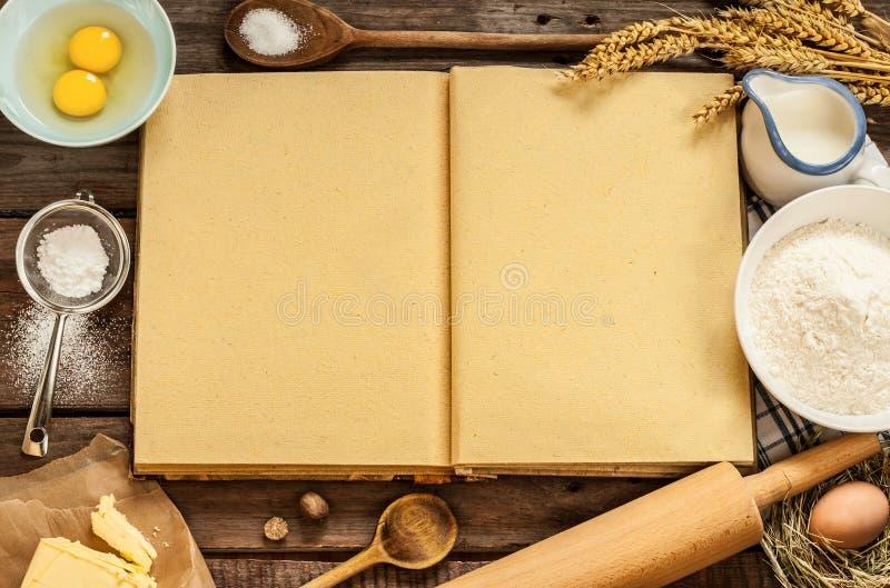 Αγροτικά συστατικά κέικ ψησίματος κουζινών και κενό βιβλίο μαγείρων στοκ εικόνες