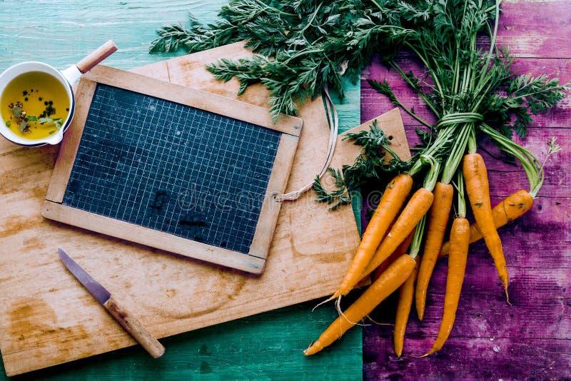 Αγροτικά φρέσκα υγιή καρότα με μια κενή πλάκα στοκ εικόνα
