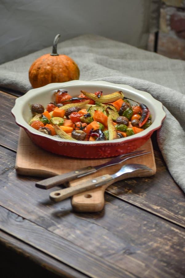 Αγροτική ακόμα ζωή των ψημένων στη σχάρα λαχανικών και σε ένα μεγάλο κεραμικό πιάτο και τις συσκευές σε ένα ξύλινο υπόβαθρο διάστ στοκ εικόνα με δικαίωμα ελεύθερης χρήσης