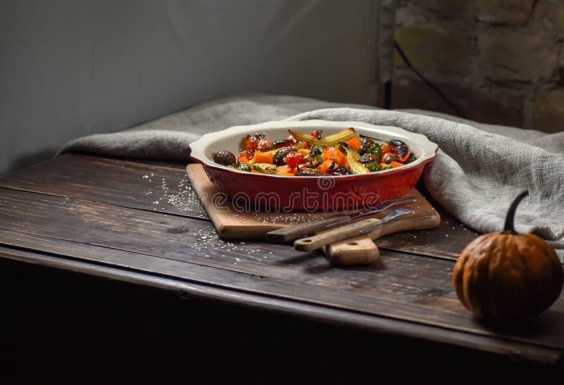 Αγροτική ακόμα ζωή των ψημένων στη σχάρα λαχανικών και σε ένα μεγάλο κεραμικό πιάτο και τις συσκευές σε ένα ξύλινο υπόβαθρο διάστ στοκ εικόνες