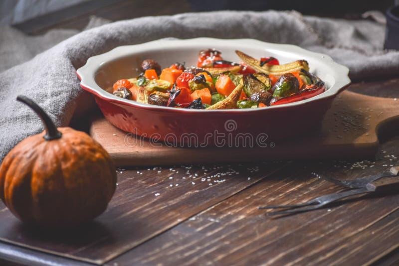 Αγροτική ακόμα ζωή των ψημένων στη σχάρα λαχανικών και σε ένα μεγάλο κεραμικό πιάτο και τις συσκευές σε ένα ξύλινο υπόβαθρο διάστ στοκ εικόνες με δικαίωμα ελεύθερης χρήσης