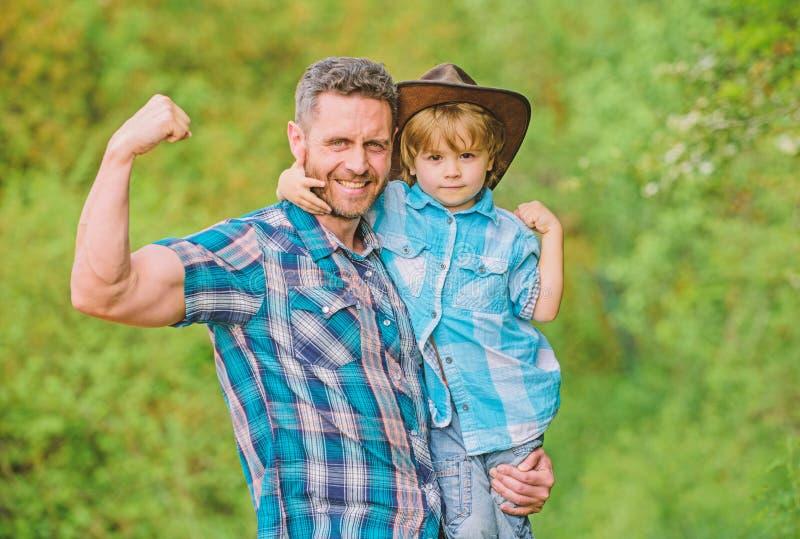 Αγροτική οικογένεια Αυξανόμενος χαριτωμένος κάουμποϋ Μικρός αρωγός στον κήπο Μικρό παιδί και πατέρας στο υπόβαθρο φύσης Πνεύμα στοκ εικόνα