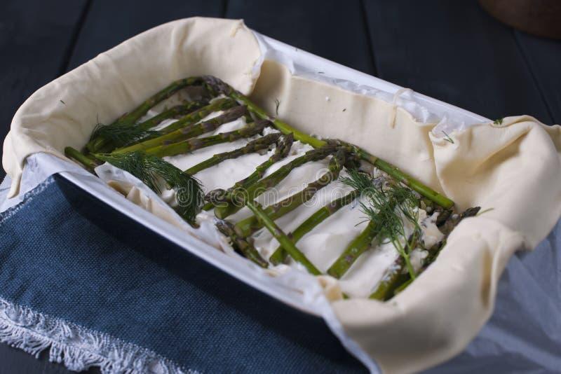Αγροτική πίτα με το σπαράγγι και το τυρί, με τα φρέσκα χορτάρια σε ένα ελαφρύ υπόβαθρο στοκ φωτογραφία με δικαίωμα ελεύθερης χρήσης