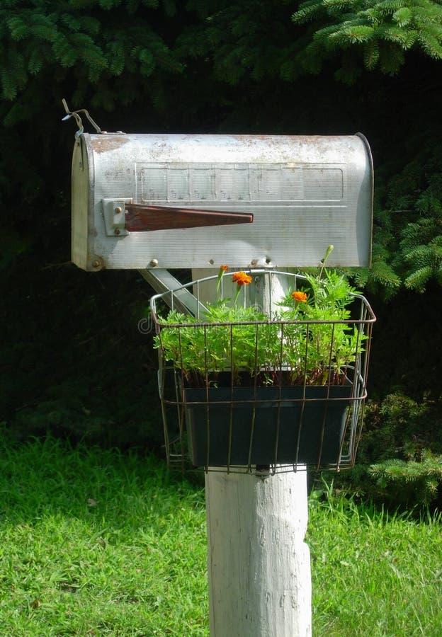 Αγροτική ταχυδρομική θυρίδα με το κιβώτιο λουλουδιών στοκ φωτογραφία