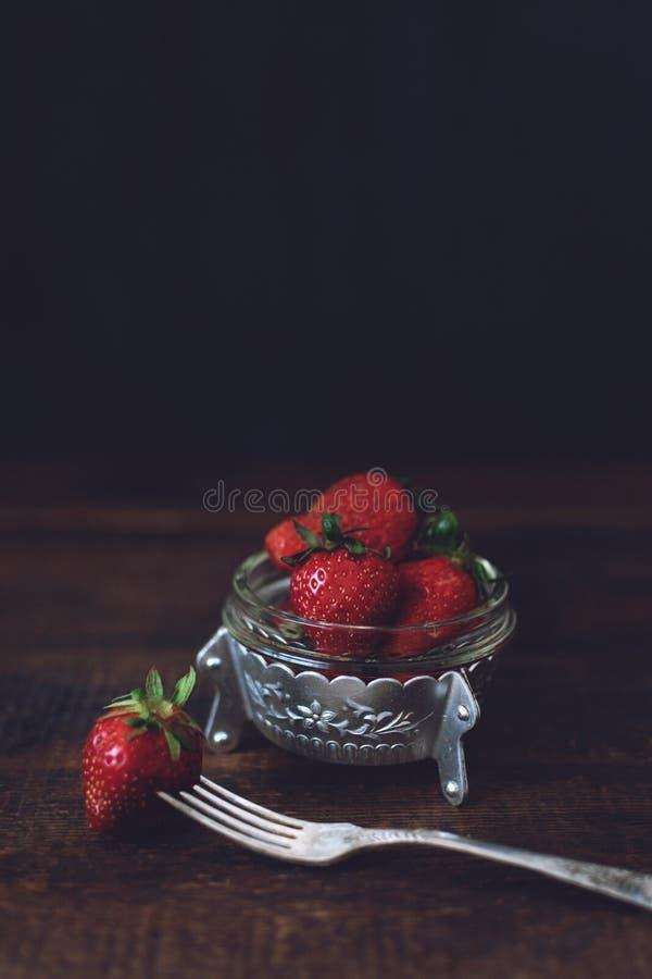Αγροτική φρέσκια οργανική φράουλα στο κύπελλο μετάλλων και δίκρανο στο σκοτεινό ξύλινο αγροτικό πίνακα Κόκκινη ακατέργαστη φράουλ στοκ εικόνα με δικαίωμα ελεύθερης χρήσης
