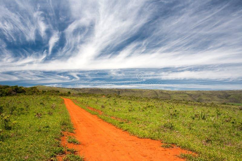 Αγροτικός πορτοκαλής βρώμικος δρόμος με το μπλε ουρανό και το μακρινό ορίζοντα στοκ εικόνα