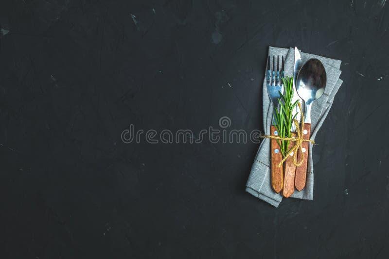 Αγροτικό εκλεκτής ποιότητας σύνολο μαχαιριού μαχαιροπήρουνων, κουτάλι, δίκρανο Μαύρο υπόβαθρο συγκεκριμένης επιφάνειας πετρών στοκ εικόνες
