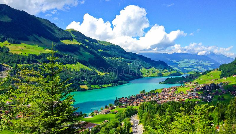 Αγροτικό ελβετικό τοπίο από την άποψη παραθύρων γύρου τραίνων, γραφική εικόνα ως ζωγραφική του χωριού Lungern και λίμνη στοκ εικόνα με δικαίωμα ελεύθερης χρήσης