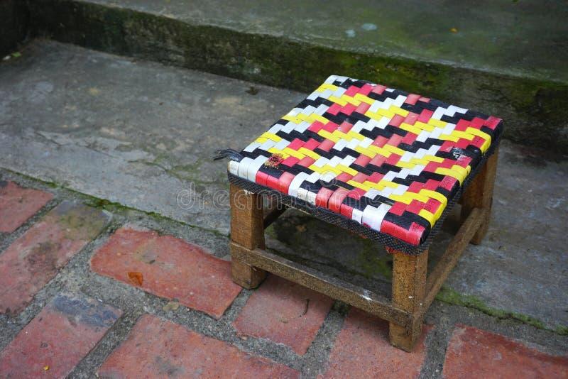 Αγροτικό ξύλινο σκαμνί με το ζωηρόχρωμο υφαμένο κάθισμα στην οδό σε Luang Prabang, Λάος στοκ φωτογραφία με δικαίωμα ελεύθερης χρήσης